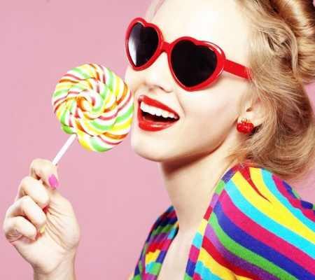8354453 - glamourous girl wearing heart shaped sunglasses holding lollipop
